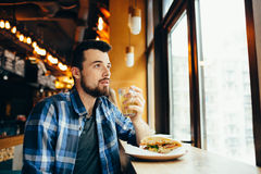 Young man is sitting in the restaurant and taste a warm drink. Concentrated handsome guy holding cup with tea with one hand and looking at window Royalty Free Stock Photos