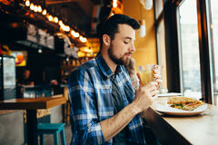 Young man is sitting in the restaurant and taste a warm drink. Royalty Free Stock Photography