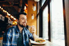 Young man is sitting in the restaurant and taste a warm drink. Young man is sitting in the restaurant and taste a drink. Smiling guy holding cup with warm tea Royalty Free Stock Image