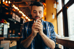 Young man is sitting in the restaurant and tasting a warm drink. Young man with beard is sitting in the restaurant near window and tasting a warm drink. He is Stock Photography