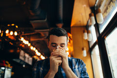 Young man is sitting in the restaurant and tasting a warm drink. Young guy in checkered shirt is sitting in the restaurant near window and tasting a warm drink Royalty Free Stock Photo