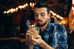 Young man is sitting in the restaurant and tasting a warm drink. Handsome guy is holding cup with both hands and going to try that tea. Close-up Stock Photos
