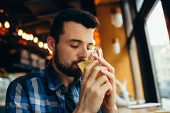 Young man is sitting in the restaurant and tasting a warm drink. Young student is sitting in the restaurant and tasting a warm drink. Attractive man is near Stock Photos