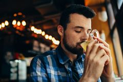 Young man is sitting in the restaurant and tasting a warm drink. Royalty Free Stock Image