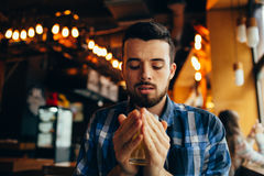 Young man is sitting in the restaurant and tasting a warm drink. Young student is sitting in the restaurant right in front of camera and tasting a warm tea. He Stock Images