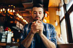 Young man is sitting in the restaurant and tasting a warm drink. Young student is sitting in the restaurant and tasting a warm tea. Attractive guy with beard Royalty Free Stock Photo
