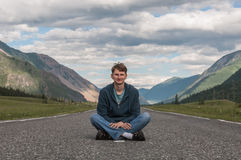 Young man sitting road mountains Royalty Free Stock Images