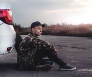 Young man sitting on the road near the car. In the evening stock photos