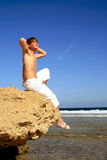 Young man sitting on a rock. With a great view over the sea Royalty Free Stock Photos