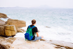 Young man sitting on the rock with backpack Stock Photos