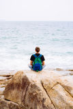 Young man sitting on the rock with backpack Royalty Free Stock Photography