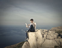 Young man sitting on a rock and using a tablet Royalty Free Stock Photos