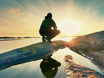 Young man sitting on a rock watching a gorgeous sunset on the sea.  Hiker alone enjoy evening Stock Photos
