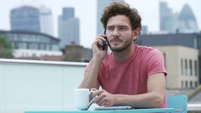 Young Man Sitting On Roof Terrace Talking On Mobile Phone Stock Photos