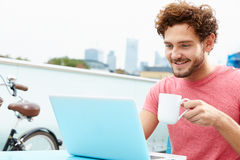 Young Man Sitting On Roof Terrace Using Laptop Stock Photo