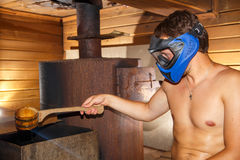Young man sitting in sauna in paintball mask. With pot in his hand Royalty Free Stock Image