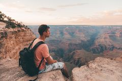 Young man sitting by the scenic view of stunning red sandstone hoodoos. In Bryce Canyon National Park in Utah, USA Royalty Free Stock Photos