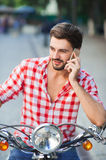 Young man sitting on scooter and holding mobile phone Royalty Free Stock Photo