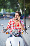 Young man sitting on scooter and holding mobile phone Royalty Free Stock Photography