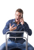 Young man sitting and screaming during phone. Attractive young man sitting and screaming during phone conversation, isolated on white Royalty Free Stock Photo
