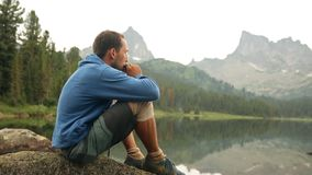 A young man sitting on the shore of a mountain lake and playing the harmonica. stock video footage