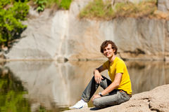 A young  man sitting on the shores of Lake Stock Photography