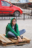 Young man sitting on a sidewalk Stock Image