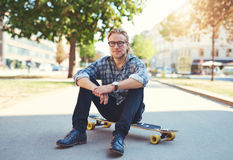Young man sitting on skateboard Stock Photo