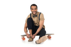 Young man sitting on skateboard and tying shoelaces. Smiling young man sitting on skateboard and tying shoelaces royalty free stock photography