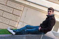 Young man sitting on slope steps Royalty Free Stock Image