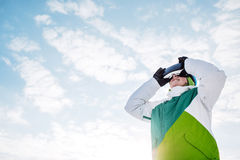 Young man sitting on the snow with snowboard and vr glasses Royalty Free Stock Photos