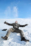 Young man sitting on snow and throw him upwards. And makes merry Royalty Free Stock Image