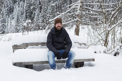 Young man is sitting on a snowy park bench Royalty Free Stock Images
