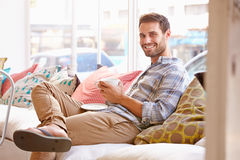 Young man sitting on sofa in a cafe Royalty Free Stock Photos