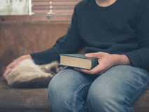 Young man sitting on a a sofa with a cat and a big book Royalty Free Stock Photography
