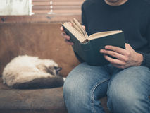 Young man sitting on sofa with cat is reading Royalty Free Stock Images