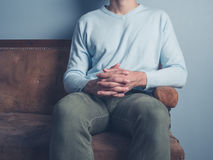 Young man sitting on sofa with hands folded Stock Photos