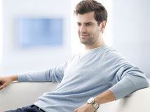 Young man sitting on sofa Stock Photography