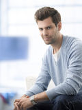 Young man sitting on sofa at home Stock Photography