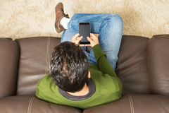 Young man sitting on sofa. Overhead view, brown couch. royalty free stock images