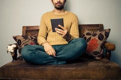Young man sitting on sofa reading on tablet Royalty Free Stock Photography