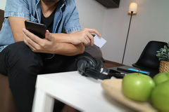 young man is sitting on sofa shopping on line with smart phone l Royalty Free Stock Photos