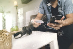 young man is sitting on a sofa shopping on line with smart phone Stock Photography