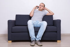 Young man sitting on sofa and talking on mobile phone Stock Photos