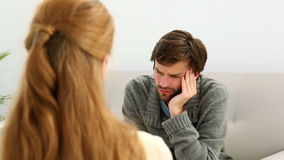 Young man sitting on sofa talking to his therapist