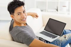 Young Man sitting in sofa and using  laptop Stock Images