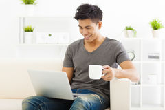 Young Man sitting in sofa and using  laptop Royalty Free Stock Photos