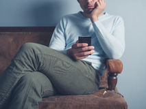 Young man sitting on sofa and using smart phone Royalty Free Stock Photography