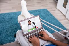 Man Video Conferencing With Doctor On Laptop stock photo