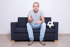 Young man sitting on sofa and watching soccer on tv at home Stock Photo